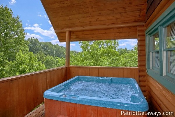Hot tub on a covered deck surrounded by woods at Hanky Panky, a 1-bedroom cabin rental located in Pigeon Forge