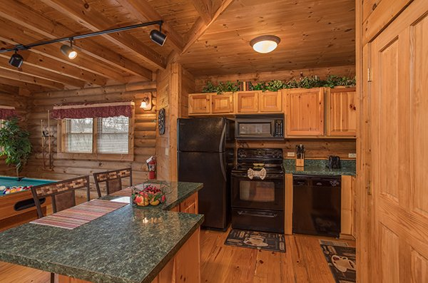 Kitchen with black appliances and an island at Hanky Panky, a 1-bedroom cabin rental located in Pigeon Forge