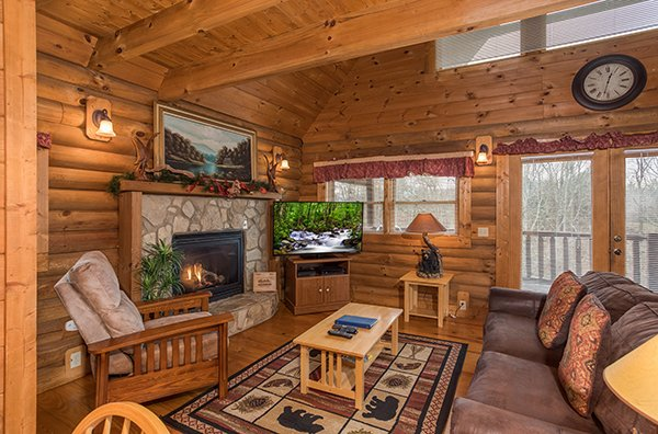 Fireplace, TV, and deck access from the living room at Hanky Panky, a 1-bedroom cabin rental located in Pigeon Forge