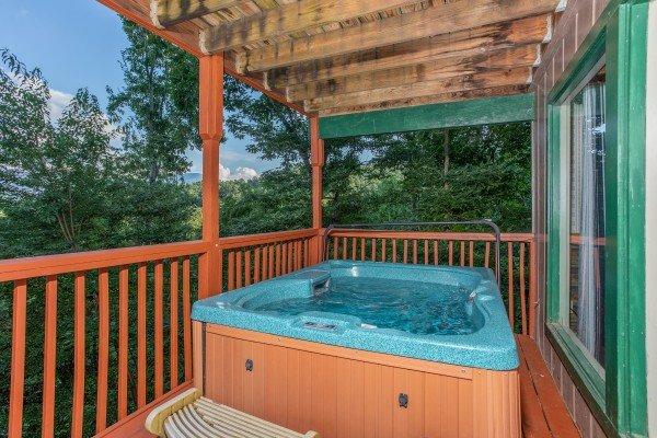 Hot tub on a covered deck at Bushwood Lodge, a 3-bedroom cabin rental located in Gatlinburg