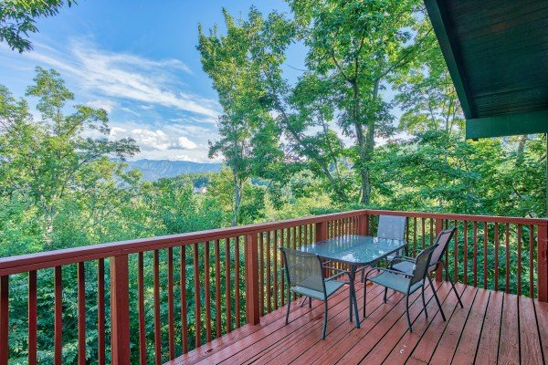 Dining space for four on the deck with mountain views at Bushwood Lodge, a 3-bedroom cabin rental located in Gatlinburg
