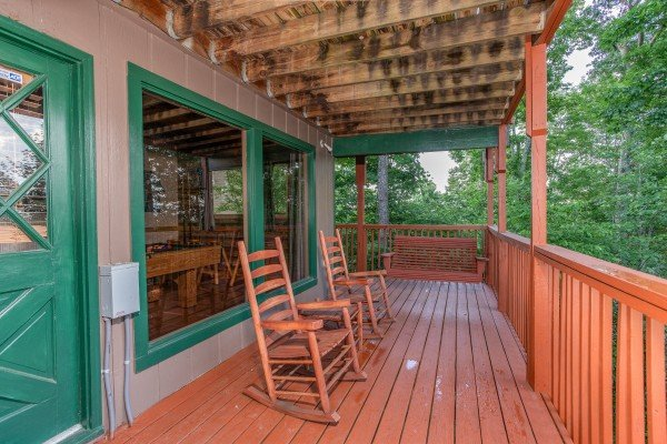 Deck with rocking chairs and a porch swing at Bushwood Lodge, a 3-bedroom cabin rental located in Gatlinburg