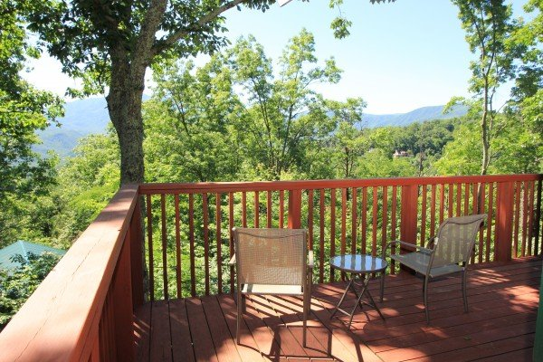 Two chairs and a drink table overlooking the mountains at Bushwood Lodge, a 3-bedroom cabin rental located in Gatlinburg