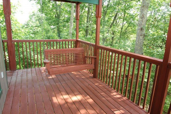 Swing on the deck at Bushwood Lodge, a 3-bedroom cabin rental located in Gatlinburg
