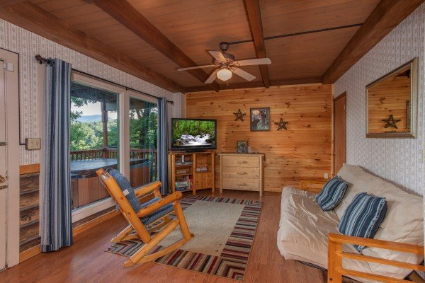 Game room with a futon, wood rocking chair, and TV at Bushwood Lodge, a 3-bedroom cabin rental located in Gatlinburg