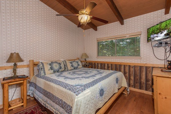 King-sized log bed in a bedroom with a TV and dresser at Bushwood Lodge, a 3-bedroom cabin rental located in Gatlinburg