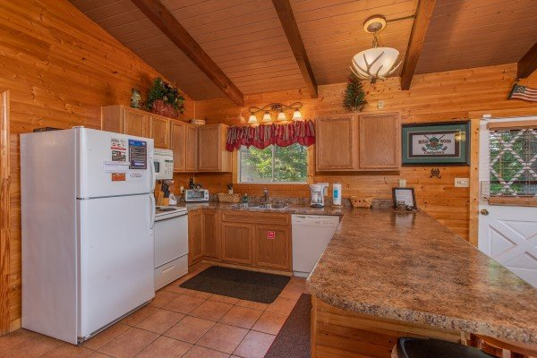 Kitchen with white appliances at Bushwood Lodge, a 3-bedroom cabin rental located in Gatlinburg