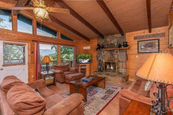 Living room with couch, loveseat, and chair, floor-to-ceiling windows, and a fireplace at Bushwood Lodge, a 3-bedroom cabin rental located in Gatlinburg