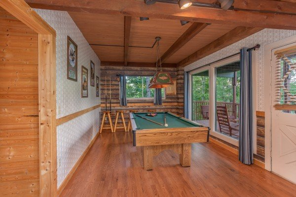 Green felted pool table in a game room at Bushwood Lodge, a 3-bedroom cabin rental located in Gatlinburg