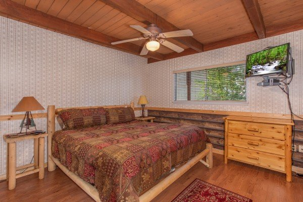 Bedroom with a king-sized log bed, dresser, and television at Bushwood Lodge, a 3-bedroom cabin rental located in Gatlinburg