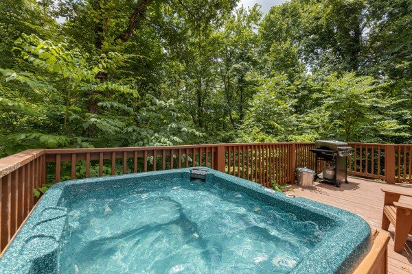 Hot tub and grill on a deck at Around the Bend, a 3 bedroom cabin rental located in Pigeon Forge