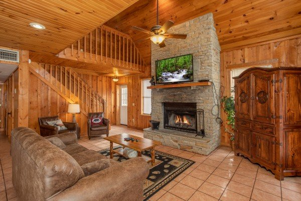 Living room with stone fireplace and TV at Around the Bend, a 3 bedroom cabin rental located in Pigeon Forge