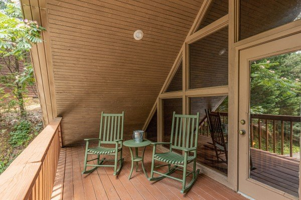 Upper deck with rocking chairs & a table at Around the Bend, a 3 bedroom cabin rental located in Pigeon Forge