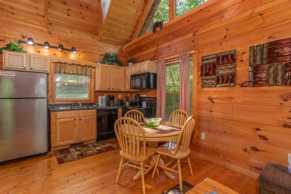 Dining space for four and kitchen at Swept Away in the Smokies, a 1 bedroom cabin rental located in Pigeon Forge
