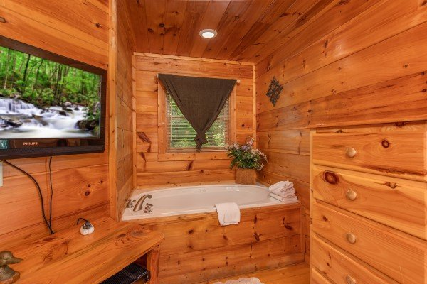 Bedroom with a TV, dresser, and in room jacuzzi at Swept Away in the Smokies, a 1 bedroom cabin rental located in Pigeon Forge