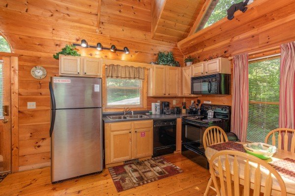 Kitchen and dining space on the main floor at Swept Away in the Smokies, a 1 bedroom cabin rental located in Pigeon Forge