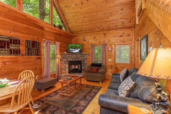 Living room with fireplace and TV at Swept Away in the Smokies, a 1 bedroom cabin rental located in Pigeon Forge