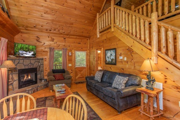 Living room with fireplace, TV, sofa, and chair at Swept Away in the Smokies, a 1 bedroom cabin rental located in Pigeon Forge