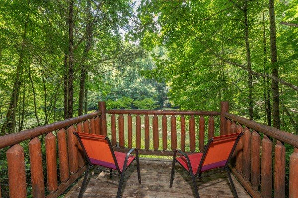 Two chairs on the lower deck overlooking the stream at Swept Away in the Smokies, a 1 bedroom cabin rental located in Pigeon Forge