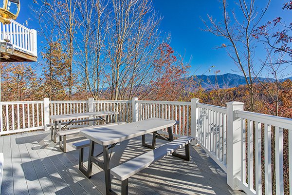 Two picnic tables on the deck overlooking the Smoky Mountains at Chalet Mignon, an 8-bedroom cabin rental located in Gatlinburg