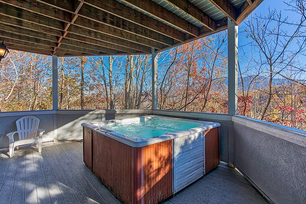 Hot tub on a covered deck with winter mountain views at Chalet Mignon, an 8-bedroom cabin rental located in Gatlinburg