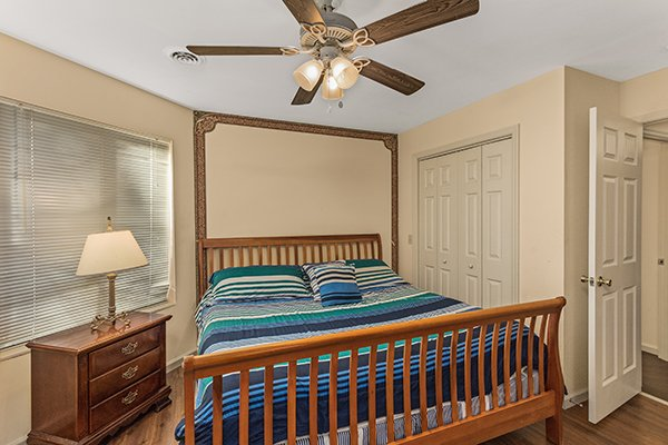 Bedroom with a king-sized sleigh bed and deck access at Chalet Mignon, an 8-bedroom cabin rental located in Gatlinburg