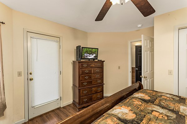 Bedroom with a dresser, television, and deck access at Chalet Mignon, an 8-bedroom cabin rental located in Gatlinburg