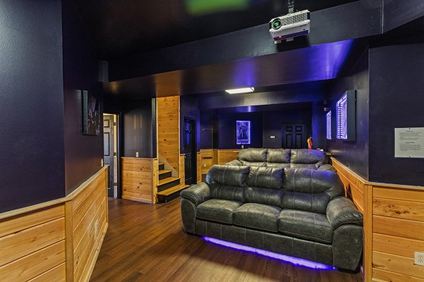 Theater room seating and blacklighting at Chalet Mignon, an 8-bedroom cabin rental located in Gatlinburg