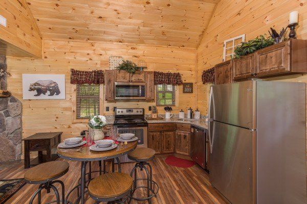 Dining space for four in the kitchen with stainless appliances at Gatlinburg Treehouse, a 1-bedroom cabin rental located in Gatlinburg