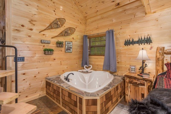 Heart-shaped jacuzzi in the studio bedroom at Gatlinburg Treehouse, a 1-bedroom cabin rental located in Gatlinburg