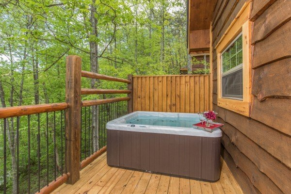 Hot tub on a porch with privacy fence at Gatlinburg Treehouse, a 1-bedroom cabin rental located in Gatlinburg