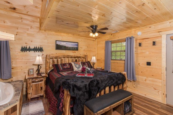 King-sized bed in the studio living room at Gatlinburg Treehouse, a 1-bedroom cabin rental located in Gatlinburg