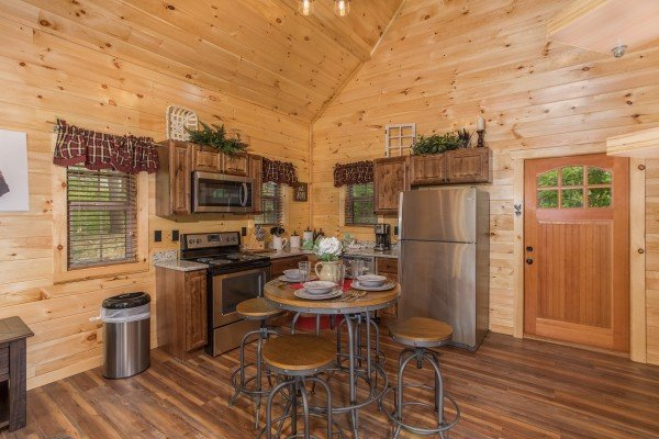 Table with seating for four in the kitchen with stainless appliances at Gatlinburg Treehouse, a 1-bedroom cabin rental located in Gatlinburg