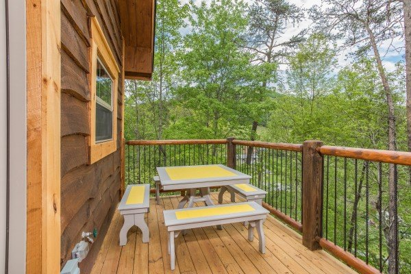 Outdoor dining space for four on the deck at Gatlinburg Treehouse, a 1-bedroom cabin rental located in Gatlinburg