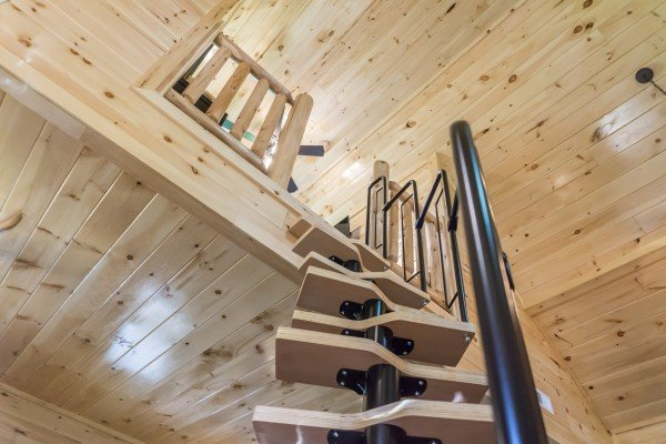 Spiral staircase leading to the loft at Gatlinburg Treehouse, a 1-bedroom cabin rental located in Gatlinburg