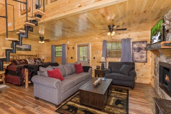 Studio style living room with a sofa, chair, fireplace, TV, king bed, and jacuzzi at Gatlinburg Treehouse, a 1-bedroom cabin rental located in Gatlinburg