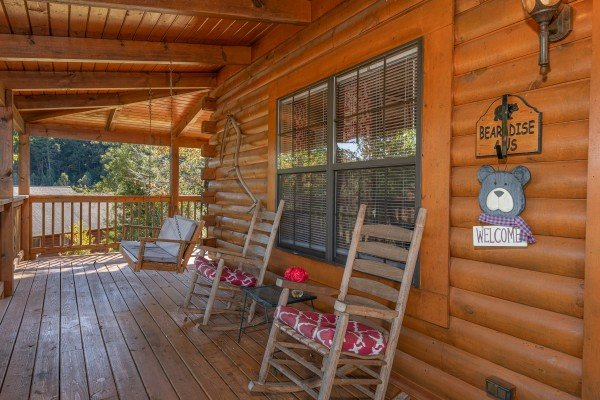 Front porch with swing and rocking chairs at Bearadise 4 Us, a 3 bedroom cabin rental located in Pigeon Forge