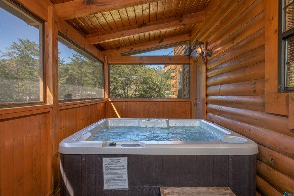 Hot tub on a covered deck at Bearadise 4 Us, a 3 bedroom cabin rental located in Pigeon Forge