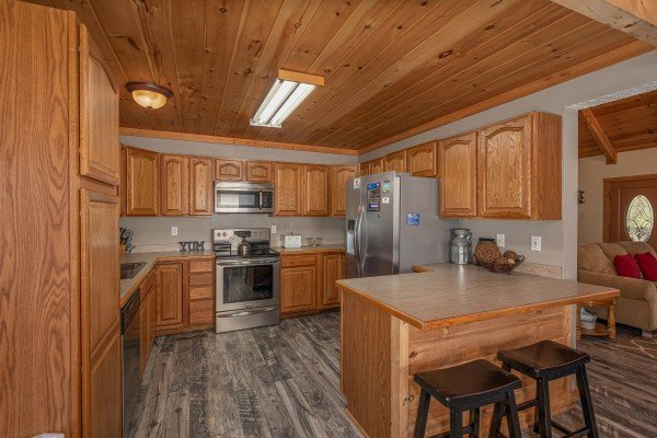 Kitchen with stainless appliances and a breakfast bar at Bearadise 4 Us, a 3 bedroom cabin rental located in Pigeon Forge