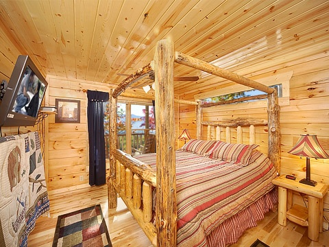 first floor king bedroom with log canopy bed at natural wonder a 4 bedroom cabin rental located in gatlinburg