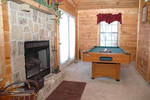 bedroom fireplace and pool table  at whispering creek a 1 bedroom cabin rental located in gatlinburg