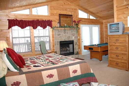 master bedroom with fireplace at whispering creek a 1 bedroom cabin rental located in gatlinburg