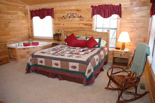 master bedroom with king bed and jacuzzi at whispering creek a 1 bedroom cabin rental located in gatlinburg
