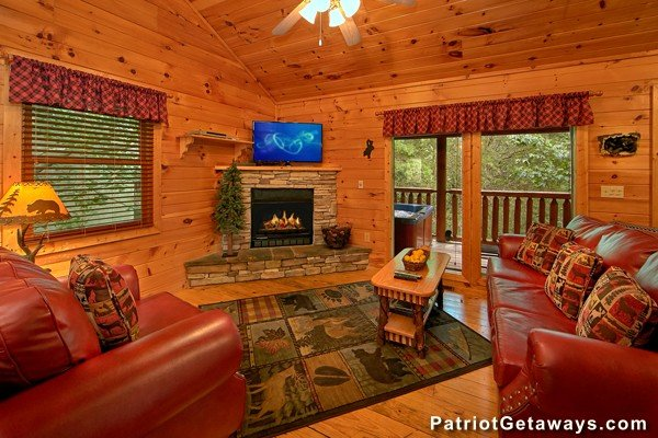Corner stacked stone fireplace with television above in the living room at Bear House Rock, a 3-bedroom cabin rental located in Pigeon Forge