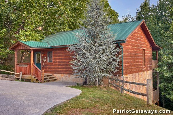 Flat paved parking pad and front exterior at Bear House Rock, a 3-bedroom cabin rental located in Pigeon Forge