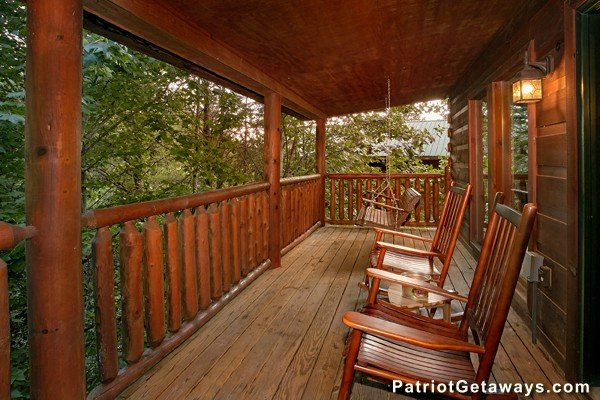 Front porch with rockers and a swing at Bear House Rock, a 3-bedroom cabin rental located in Pigeon Forge