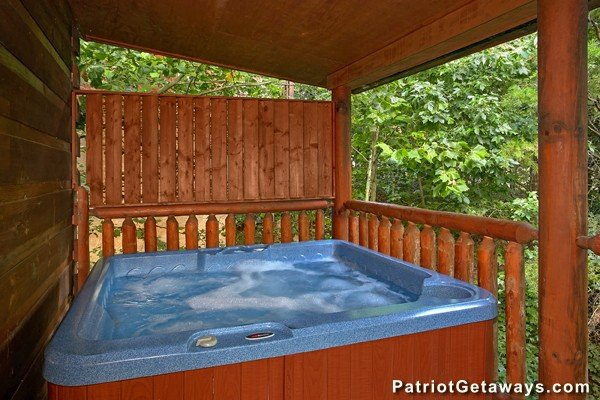 Hot tub with a privacy fence on a covered deck at Bear House Rock, a 3-bedroom cabin rental located in Pigeon Forge