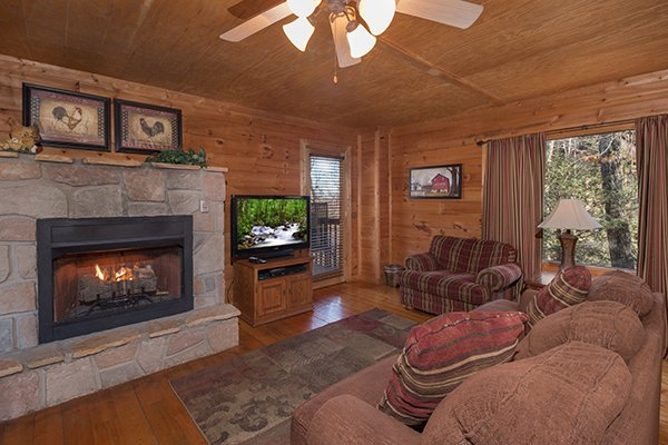Living room fireplace and TV at Sunny Side Up, a 2 bedroom cabin rental located in Gatlinburg