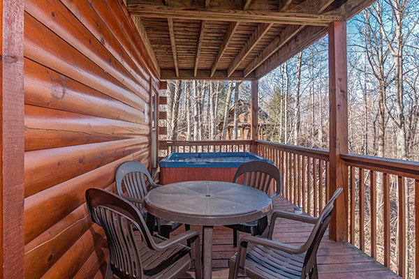 Dining space for four on a covered deck at Sunny Side Up, a 2 bedroom cabin rental located in Gatlinburg