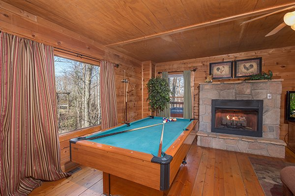 Pool table near a fireplace in the living room at Sunny Side Up, a 2 bedroom cabin rental located in Gatlinburg